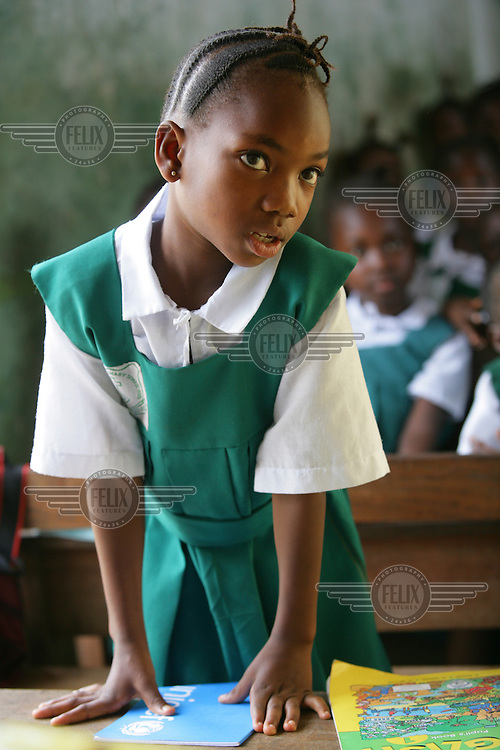 A girl stands in a class at a primary school in Freetown, supported by UNICEF.