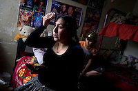 29 year old wrestler Martha La Altena (fighting name), Yenny Wilma Maraz (real name) sits in her daughters' room getting ready for a fight, with posters of famous wrestlers on the wall. Yenny is a Cholita, a wrestler of native Aymara descent. When Cholitas fight they wear traditional costume. Yenny fights with the lucha libre (free wrestling) group Los Titanes del Ring. ..