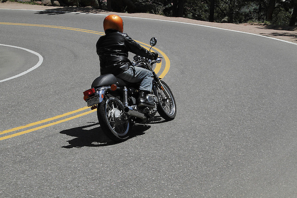 Caucasian male motorcycling downhill on Lookout Mountain Road west of Denver, Colorado, USA .  John leads private photo tours in Boulder and throughout Colorado. Year-round.