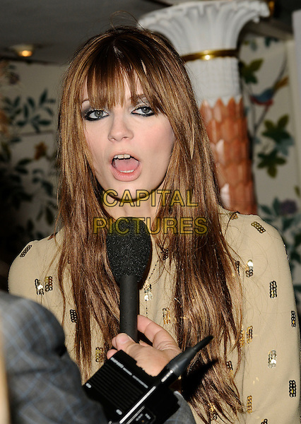 MISCHA BARTON.Fifi UK Fragrance Awards 2009, The Dorchester hotel, London, England..April 22nd 2009.half length gold yellow microphone mouth open funny face fringe bangs eyeliner sequins sequined.CAP/CAN.©Can Nguyen/Capital Pictures.