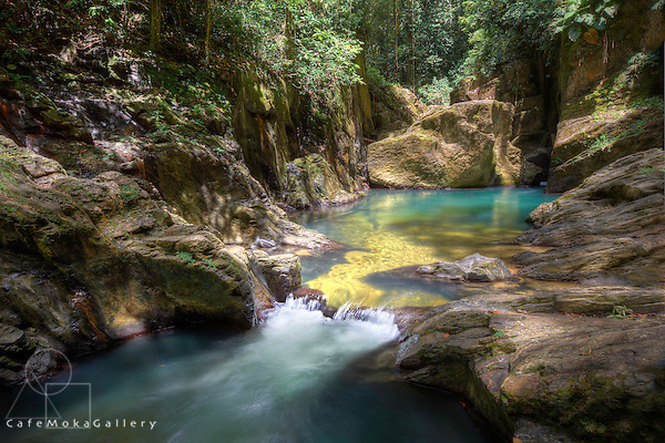 Dappled sunlight shows the rocks and turquoise pool one of the Three Pools of the Marianne river