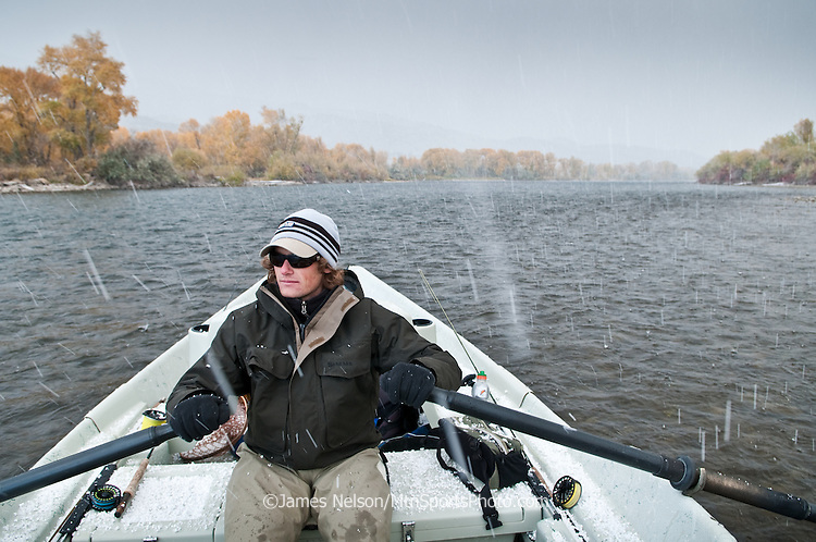 Erik Hallgren rows a drift boat as snow pellets (i.e., graupel) fall during a trout fishing trip on the South Fork of the Snake River, Idaho.