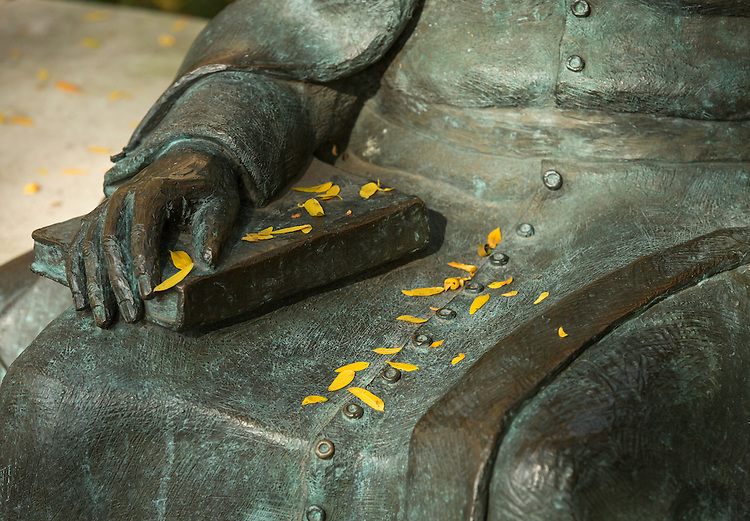Fallen leaves pepper the statue of St. Vincent de Paul at St. Vincent's Circle on the Lincoln Park campus. The statue, featuring St. Vincent de Paul talking with two students, is located just to the east of the Quad between the Richardson Library and the Schmitt Academic Center.  week of  Oct. 1, 2014.  (DePaul University/Jamie Moncrief)