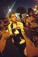 EGITTO, IL CAIRO 9/10 settembre 2011: assalto all'ambasciata israeliana. Migliaia di manifestanti egiziani, ancora infuriati per l'uccisione di cinque guardie di frontiera egiziane da parte dell'esercito israeliano, hanno fatto irruzione nella sede diplomatica israeliana e sono stati poi sgomberati da esercito e polizia egiziana. Nell'immagine: un giovane manifestante mostra la fotografia di un uomo. Dietro di lui un poliziotto e altri manifestanti la sera degli scontri.<br /> Egypt attack to the Israeli embassy  Attaque &agrave; l'ambassade israelienne Caire