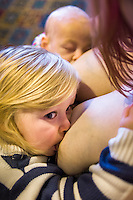A mother tandem feeds her two children, one about one about twelve weeks old and one about 28 months old, at a sling meet held in the family restaurant and play area in a pub.