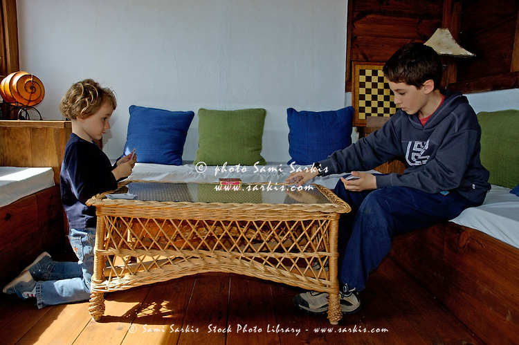 Little girl playing cards with her brother, Tarifa, Andalusia, Spain.