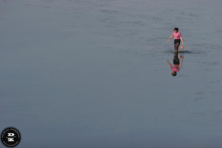 A woman walks through the Chongyang river in WuyiShan, China.   Photograph by Douglas ZImmerman
