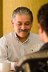 Hispanic man playing cards