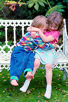 A five year old girl hugging her younger brother