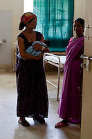 A female community health worker looks on as Amrita Rokya, 18, cradles her 2-day-old baby in the Bardia District Hospital, one hour's walk from her village in Bardia, Western Nepal, on 29th June 2012. In Bardia, StC works with the district health office to build the capacity of female community health workers who are on the frontline of health service provision like ante-natal and post-natal care, and working together against child marriage and teenage pregnancy especially in rural areas. Photo by Suzanne Lee for Save The Children UK