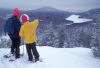snowshoeing, Vermont, VT, Mother and daughter snowshoeing on Owl's Head overlooking the frozen Kettle Pond in Groton State Forest in winter.