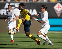 CHARLOTTE, NC - JULY 20: Bukayo Saka #77 is chased by Lorenzo Venuti #2 during a game between ACF Fiorentina and Arsenal at Bank of America Stadium on July 20, 2019 in Charlotte, North Carolina.