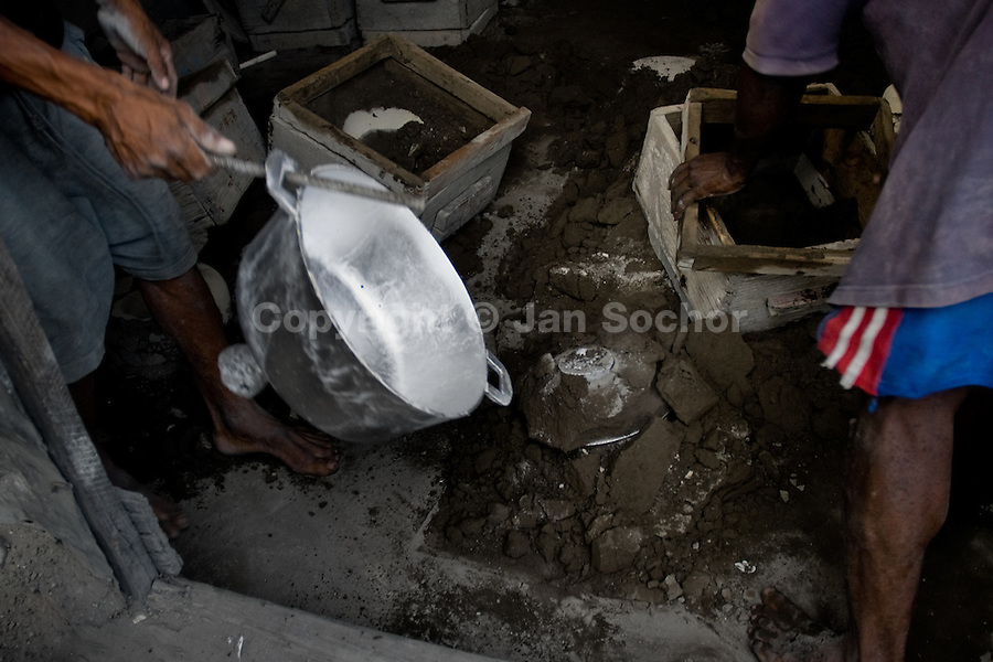 A Haitian man holds a hot aluminium pot released from the shell in the aluminium recycling shop on the street of Port-au-Prince, Haiti, 11 July 2008.