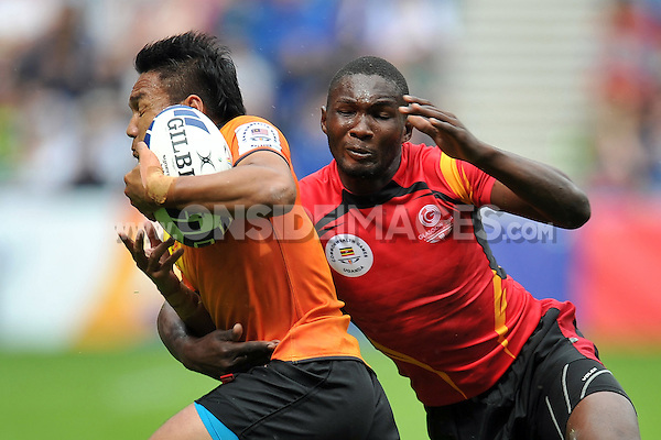 Muhammad Faridzal Ismail of Malaysia is tackled by Govle Ramathan of Uganda in the Men's Rugby Sevens Bowl Quarter-final between Malaysia and Uganda. Day four, Glasgow 2014 Commonwealth Games, Rugby Sevens, on July 27, 2014 at the Ibrox Stadium in Glasgow, Scotland. Photo by: Patrick Khachfe / Onside Images