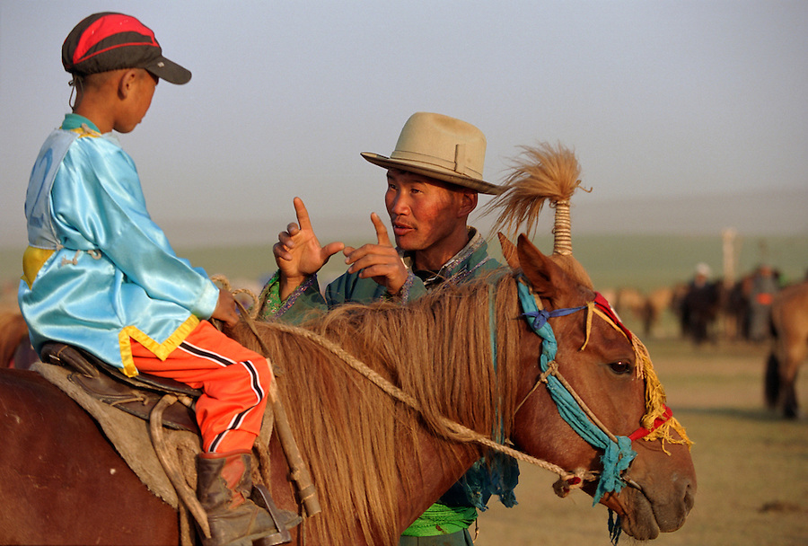 Khui Doloon Khudag, Mongolia, July 2003..Competitors & spectators at the horse racing in the national Naadam 40 kilometres outside Ulaanbaatar..A coach gives last minute tactical advice to a young jockey before the race.