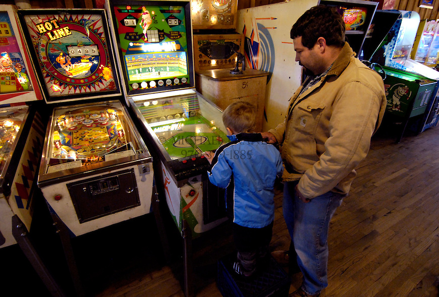 Kirk Acheson and his son Keaton, 4, of Tyler, TX, play a pinball game at the Arcade in Manitou Springs, CO. Michael Brands for The New York Times.
