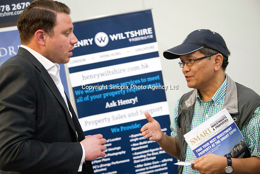 Adam Dockley, UK sales director of Henry Wiltshire, speaks to a potential buyer at the Smart International Property Investment Expo at the Hong Kong Convention and Exhibition Centre in Hong Kong. <br /> 07-08 June, 2014<br /> <br /> Photo by Tim O'Rourke / Sinopix