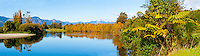 Panoramic Photo of the Reflection of Autumn Trees Lining the Takaka River in Golden Bay, South Island, New Zealand. This panoramic photo shows the reflection of autumn trees lining the Takaka River in the Golden Bay area of New Zealand. The rivers and landscapes of New Zealand are stunning all year round, but even moreso in the autumn.