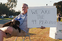 "Rik sits with his dog Mischa at the Occupy Orange County camp in Irvine, CA while holding a ""We are the 99 percent"" sign alongside a road."