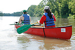 Two young women in a canoe paddle on the Fox River in Yorkville Illinois USA