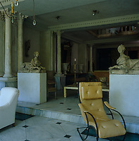 A pair of shellstone sphinxes are juxtaposed with a 19th century American rocking chair in the marble-floored living room