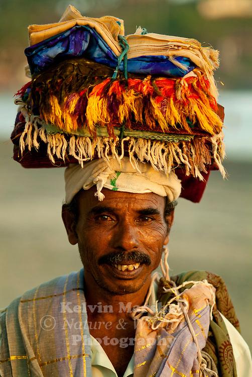 local beach hawker selling sarongs on the beach.  Kovalam Beach, Kerala, Southern India.