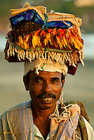 local beach hawker selling sarongs on the beach.  Kovalam Beach, Kerala, Southern India.