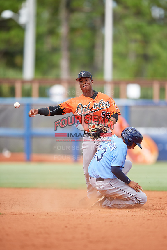 Baltimore Orioles Jean Carmona (52) throws to first base on a double play attempt as Kaleo Johnson (83) slides into second base during a Florida Instructional League game against the Tampa Bay Rays on October 1, 2018 at the Charlotte Sports Park in Port Charlotte, Florida.  (Mike Janes/Four Seam Images)