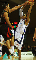 Cougars guard Paul Henare goes high trying to block Mike Efevberha during the NBL match between the Wellington Saints and Christchurch Cougars at Te Rauparaha Stadium, Porirua, Wellington, New Zealand on Saturday 4 April 2009. Photo: Dave Lintott / lintottphoto.co.nz