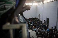 A group of Sub-Saharan illegal migrants and refugees are crowded into one section of a Surman Detention Centre, a warehouse-like facility holding as many as 2,000 detainees at any one time, making it the largest of its type on Libyan soil. The Centre serves as a distribution facility in the human trafficking supply chain, and from here inmates are re-sold to other militias on the west coast of Libya.