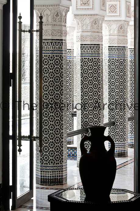 The silhouette of a terracotta vase with views of the black and white courtyard in the background