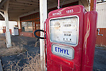 Retired red Ethyl gasoline pump with tumbleweed in front of an abandoned gas station, Orovada, Nevada.