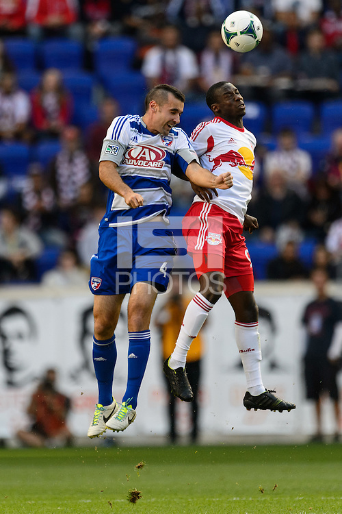 Andrew Jacobson (4) of FC Dallas goes up for a header with Bradley Wright-Phillips (99) of the New York Red Bulls. The New York Red Bulls defeated FC Dallas 1-0 during a Major League Soccer (MLS) match at Red Bull Arena in Harrison, NJ, on September 22, 2013.