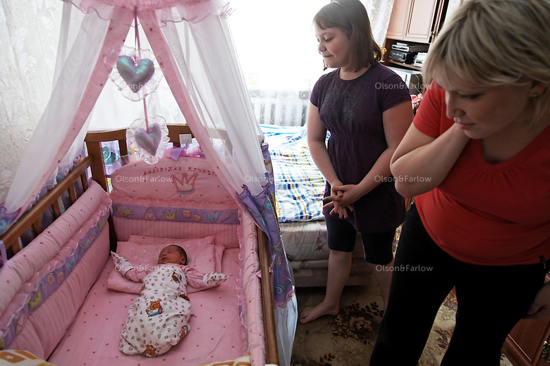 """Photographs of Yulia Smirnova and her family at their home.  Yulia had her second child at the Moscow Planning Center and Reproduction Maternity Home. Yulia made the decision on a 2nd child based on the fact that she would get """"mother's capital"""" and they could move out of the one room they share with their daughter in their mother-in-law's apartment.  Once she had the child she loved it so much she wondered why the money was the main motivation... because she was so happy to have the 2nd child..The maternity home delivers about 8000 children a year... about 20 a day or so... This is the most of any maternity hospital in Russia.  There are 117,000 delivered in 2009 in all of Moscow.  1,800,000 were born in Russia in 2009 which is 27,000 more than the deaths that year.  So Russia is basically at the replacement rate, but there are not as many breeders in the lineup moving forward... so the state has instituted a number of policies including free housing for immigrants and a one time payment of over $10,000 for a woman to have either the 2nd, 3rd or 4th baby."""