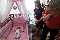 "Photographs of Yulia Smirnova and her family at their home.  Yulia had her second child at the Moscow Planning Center and Reproduction Maternity Home. Yulia made the decision on a 2nd child based on the fact that she would get ""mother's capital"" and they could move out of the one room they share with their daughter in their mother-in-law's apartment.  Once she had the child she loved it so much she wondered why the money was the main motivation... because she was so happy to have the 2nd child..The maternity home delivers about 8000 children a year... about 20 a day or so... This is the most of any maternity hospital in Russia.  There are 117,000 delivered in 2009 in all of Moscow.  1,800,000 were born in Russia in 2009 which is 27,000 more than the deaths that year.  So Russia is basically at the replacement rate, but there are not as many breeders in the lineup moving forward... so the state has instituted a number of policies including free housing for immigrants and a one time payment of over $10,000 for a woman to have either the 2nd, 3rd or 4th baby."