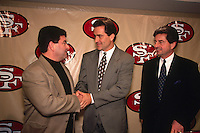 SANTA CLARA, CA - New head coach Steve Mariucci of the San Francisco 49ers is introduced to the media and shakes hands with Eddie DeBartolo (left) and Carmen Policy (right) at the 49ers facility in Santa Clara, California in 1997. Photo by Brad Mangin