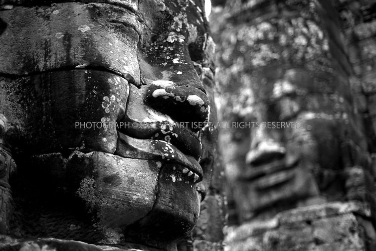 4/20/2003--Angkor Wat Temples, Siem Reap, Cambodia ..BAYON.Prasat Bayon was built in late 12th century to early 13th century, by the King Jayavarman VII, dedicated to Buddhist..BACKGROUND.The Bayon vies with Angkor Wat the favorite monument of visitors . the two evoke similar aesthetic responses yet are different in purpose, design, architecture and decoration. The dense jungle surround the temple camouflaged its position in relation to other structures at Angkor so it was not known for some time that the Bayon stands in the exact centre of the city of Angkor Thom. Even after this was known, the Bayon was erroneously connected with the city of Yasovarman I and thus dated to the ninth century. A pediment found in 1925 depicting an Avalokitesvara identified the Bayon as a Buddhist temple. This discovery moved the date of the monument ahead some 300 years to the late twelfth century. Even though the date is firmly implanted and supported by archaeological evidence, the Bayon remains one of the most enigmatic temples of the Angkor group. Its symbolism, original form and subsequent changes and constructions have not yet been untangled...The architectural scale and composition of the Bayon exude grandness in every aspects. Its elements juxtapose each other to create balance and harmony. Over 2000 large faces carved on the 54 tower give this temple its majestic character. The faces with slightly curving lips, eyes placed in shadow by the lowered lids utter not a word and yet force you to guess much, wrote P Jennerat de Beerski in the 1920s. It is generally accepted that four faces on each of the tower are images of the bodhisattva Avalokitesvara and that they signify the omnipresence of the king. The characteristics of this faces - a broad forehead, downcast eyes, wild nostrils, thick lips that curl upwards slightly at the ends-combine to reflect the famous 'smile of Angkor'....All photographs ©2003 Stuart Isett.All rights reserved.