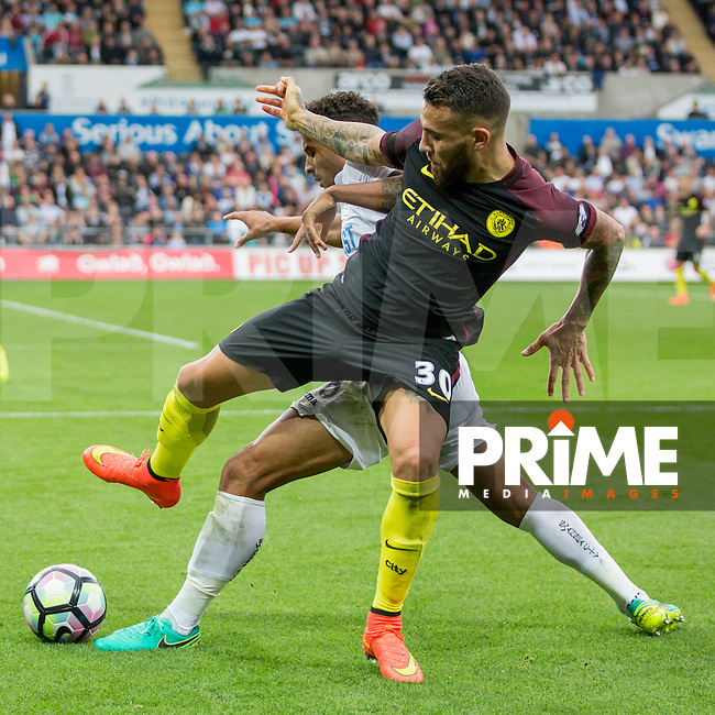 Nicolas Otamendi of Manchester City is tackled by Kyle Naughton of Swansea City during the EPL - Premier League match between Swansea City and Manchester City at the Liberty Stadium, Swansea, Wales on 24 September 2016. Photo by Mark  Hawkins.