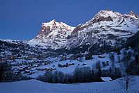 CHE, Schweiz, Kanton Bern, Berner Oberland, Grindelwald an einem Winterabend mit dem Wetterhorn 3.701 m und Schreckhorn 4.078 m | CHE, Switzerland, Bern Canton, Bernese Oberland, Grindelwald on a winter evening with Wetterhorn mountain 12.143 ft and Schreckhorn mountain 13.380 ft