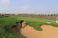 Shane Lowry (IRL) chips from a bunker at the 17th green during Sunday's Final Round of the 2014 BMW Masters held at Lake Malaren, Shanghai, China. 2nd November 2014.<br /> Picture: Eoin Clarke www.golffile.ie