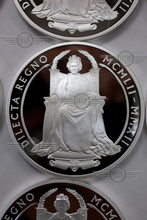 The Queen's Diamond Jubilee silver coin, freshly coined at the Royal Mint, near Llantrisant in Mid Glamorgan. As well as producing coinage for domestic use the mint also manufactures coins for around 60 countries worldwide.