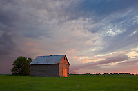 Bureau County, IL<br /> Evening light on a weathered red barn and a sky of gathering clouds
