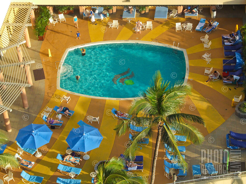 An aerial view of a relaxed crowd at a hotel swimming pool and deck in Waikiki, O'ahu.
