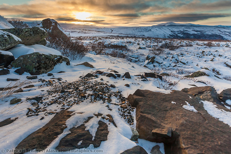 Sunset falls on the snow covered rocks on the summit of Finger mountain in Alaska's Arctic.