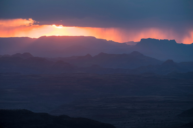 A setting sun backlights rain falling from storm clouds over the mountains west of Lalibela.