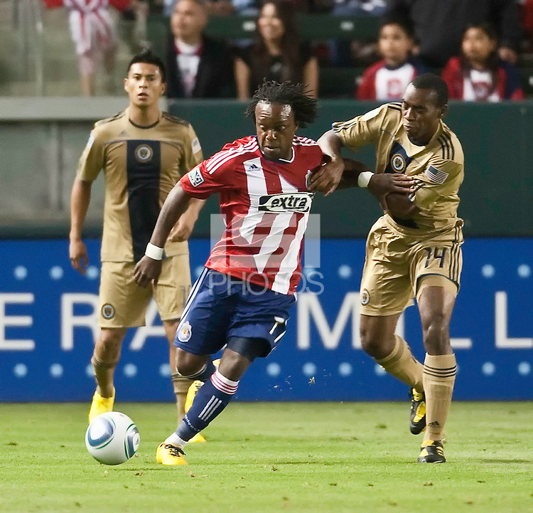 Philadelphia Union midfielder Amobi Okugo (14) tries to slow down Chivas USA forward Chukwudi Chijindu (77) during the second half of the game between Chivas USA and the Philadelphia Union at the Home Depot Center in Carson, CA, on July 3, 2010. Chivas USA 1, Philadelphia Union 1.