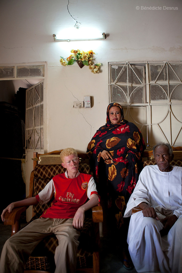 April 26, 2010  Khartoum, Sudan - Mohamed at home with his mother and grand-father. Mohamed Magdy, is a 19 year old Sudanese albino. Mohamed is finishing school and works fixing computers. He lives in Khartoum with his mother and grand-father. His father left him when he was 40 days and never came back. He says people on the street think he is usual, others think he is an angel. Albinism is a genetic condition caused by a lack of melanin in the skin, eyes and hair. Photo credit: Benedicte Desrus