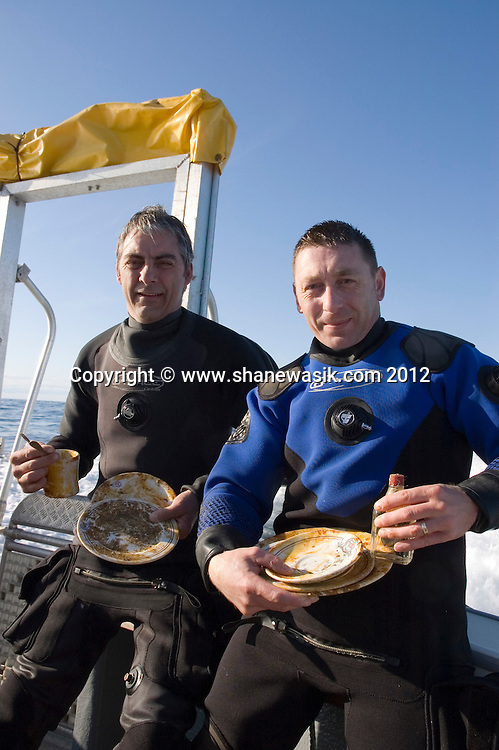 Two divers show the items recovered from a dive on a virgin wreck. This recovery was essentially in piecing together clues to enable the team to identify the wreck of the S.S. Exmouth.