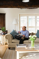 John Coles photographed seated in relaxed mode in the light and airy living room of his converted Victorian warehouse on the banks of the River Trent in Nottingham