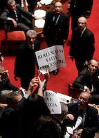 """I senatori dell'Italia dei Valori esibiscono cartelli di protesta durante una seduta nell'aula del Senato, a Roma, 20 gennaio 2010, in occasione del voto sul processo breve..A senator of Italia dei Valori party holds a sign reading """"Berlusconi go to trial"""" during a plenary session at the Senate, in Rome, 20 january 2010, prior to a vote on a bill that will shorten the length of trials..UPDATE IMAGES PRESS/Riccardo De Luca"""
